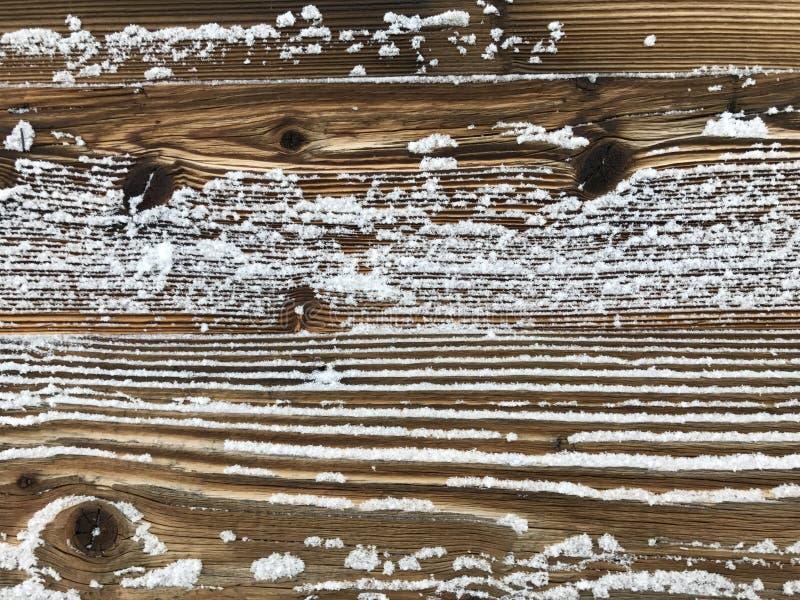 Altes Holz bedeckt mit Schneehintergrund stockfoto