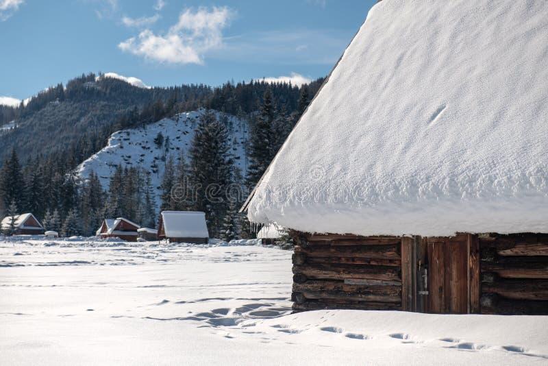Altes Holzhaus durch die Straße in einer schönen Winterlandschaft Enorme Eiszapfen hängen vom Dach stockbilder