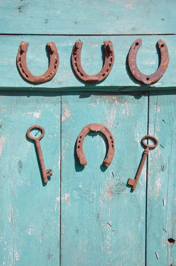 Altes Hufeisen und rostiger Schlüssel auf hölzerner alter Tür stockfotografie