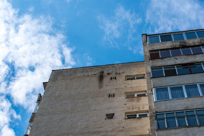 Altes konkretes Wohnungsturmgebäude in sehr schlechter Zustand, vibrierender blauer Himmel mit weißen Wolken im Hintergrund stockfotos