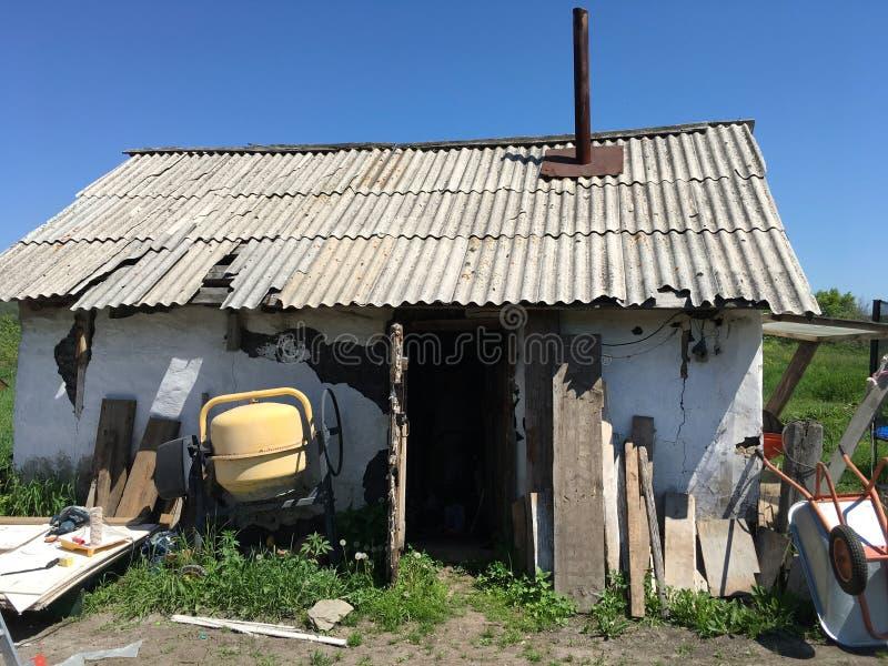 Altes ländliches Gebäude mit einem Rohr, Mischer, Brettern und einer Schubkarre stockfotografie