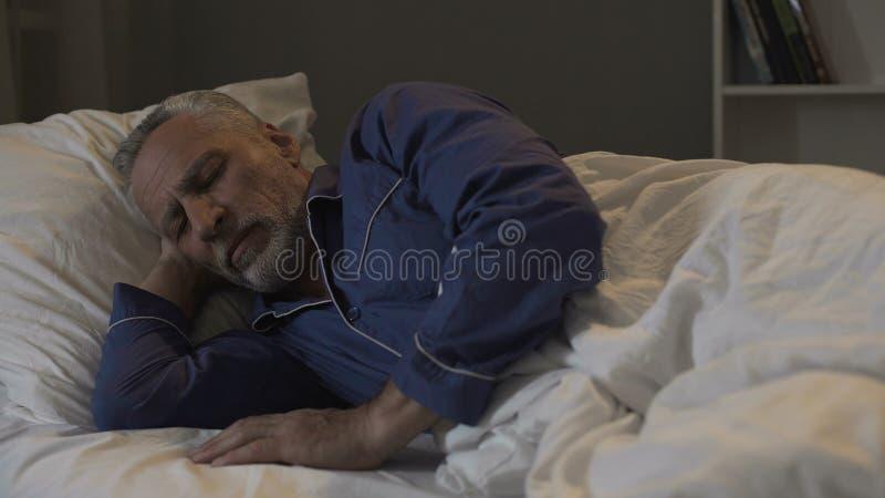 Altes männliches Lügen in seinem Bett und Schlafen, Genesungszeit und gesunder Schlaf, Nacht lizenzfreie stockfotos