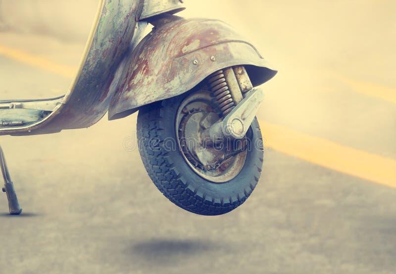 Altes Motorraddetail der Weinlese über Straßenhintergrund lizenzfreies stockbild