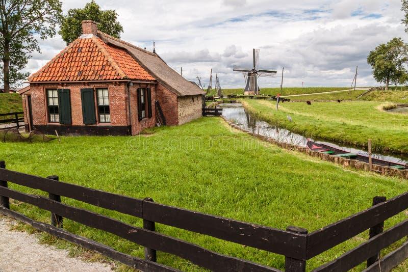 Altes niederländisches Häuschen u. Windmühle lizenzfreie stockfotografie