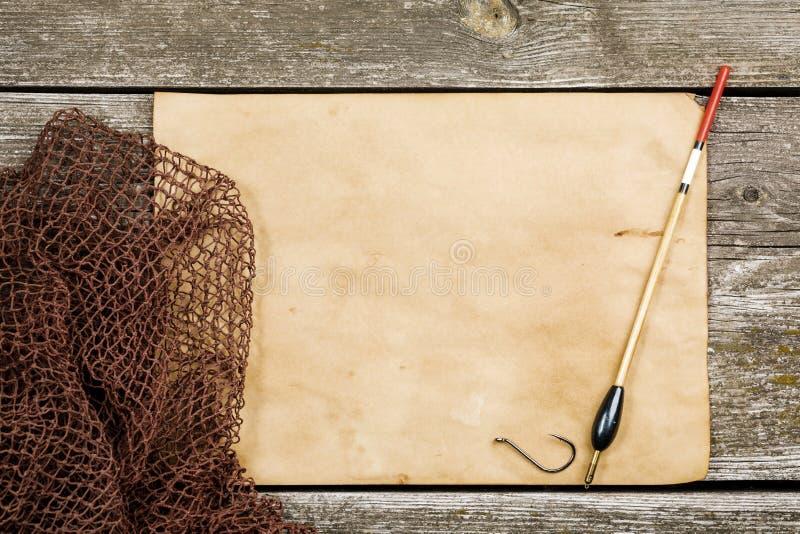 Altes Papier, Fischernetz und Schwimmer, Haken auf einem hölzernen tabl lizenzfreies stockbild