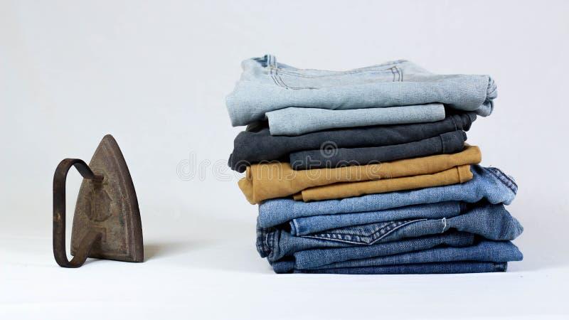 altes Plätteisen mit Jeans auf weißem Hintergrund stockfotos