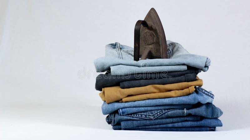 altes Pl?tteisen mit Jeans auf wei?em Hintergrund stockfotos