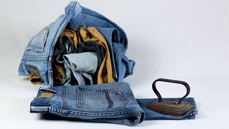 altes Pl?tteisen mit Jeans auf wei?em Hintergrund stockfotografie