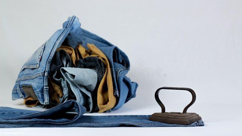 altes Pl?tteisen mit Jeans auf wei?em Hintergrund lizenzfreie stockfotos