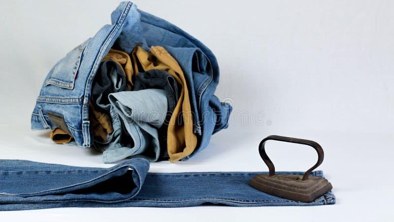 altes Pl?tteisen mit Jeans auf wei?em Hintergrund lizenzfreies stockfoto