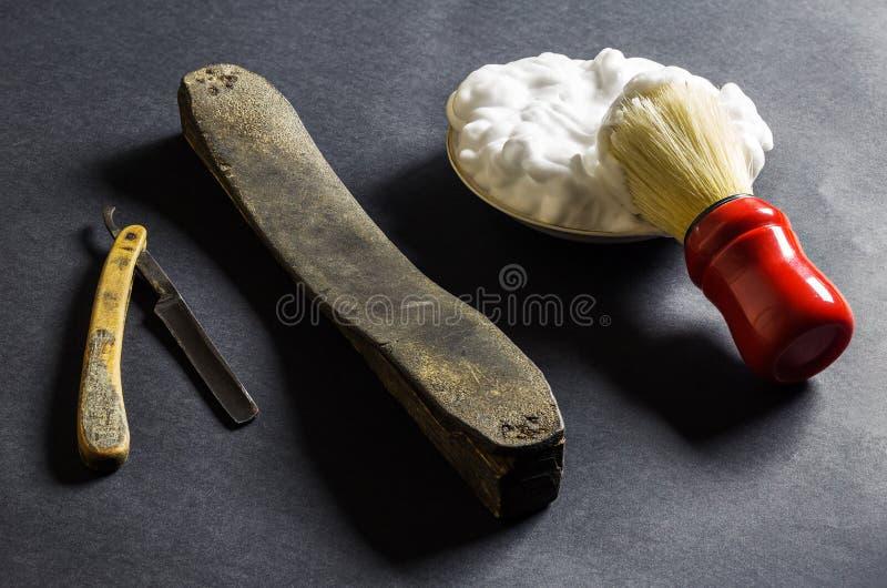 Altes Rasiermesser mit dem Schärfen des Leders, der Bürste und des Schaums lizenzfreie stockbilder