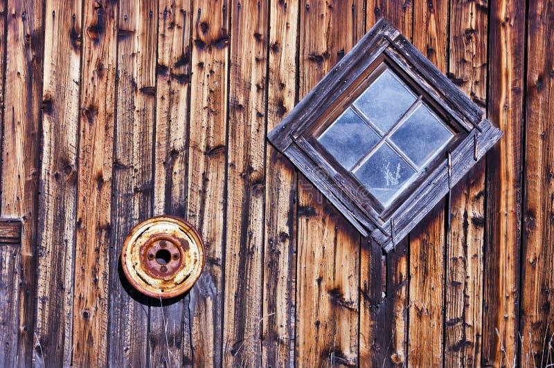 Altes rautenförmiges Stall-Fenster und verrostete Gummireifen-Felge lizenzfreies stockfoto