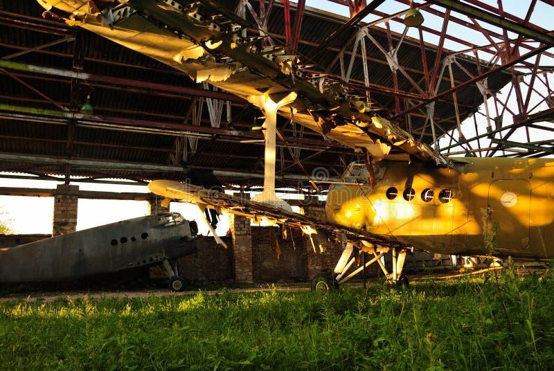 Altes Retro- gebrochenes Flugzeug in einem verlassenen Hangar stockfoto