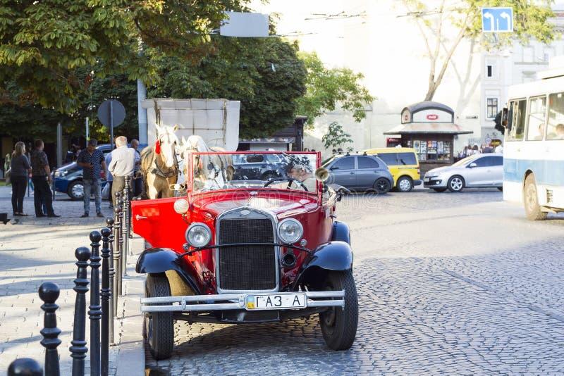 Altes Retro- sowjetisches rotes Auto GAZ auf Stadtstraße stockbilder
