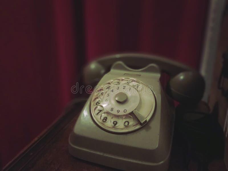 Altes Retro- Telefon auf einem Holztisch mit rotem Vorhang auf dem Hintergrund - altes Foto, Weinlesearteffekt stockbilder