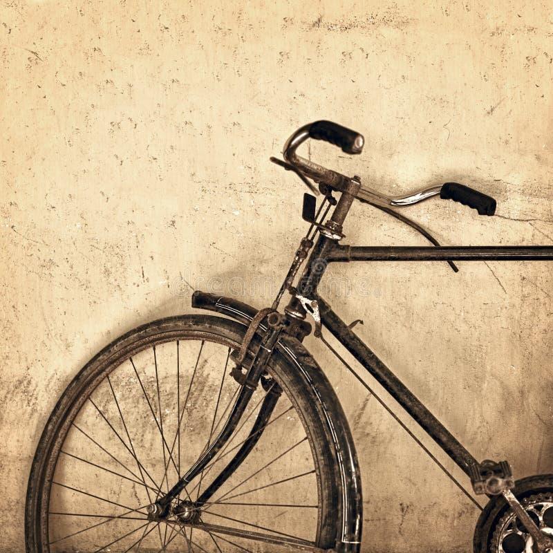 Altes rostiges Fahrrad auf Schmutzwandhintergrund lizenzfreie stockfotografie