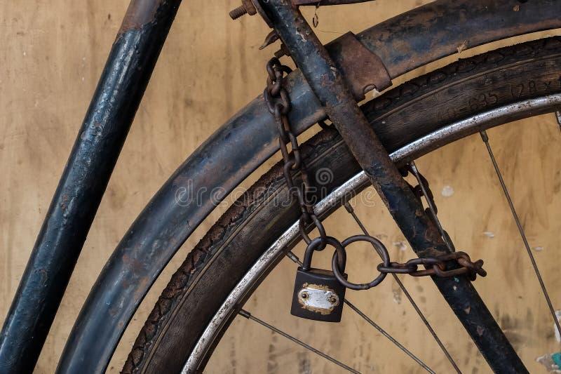 Altes rostiges Fahrrad mit Kette und Verschluss auf dem Rad stockbild
