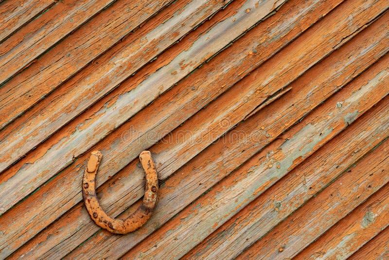 Altes rostiges Hufeisen auf einer bewaldeten Tür lizenzfreie stockfotos