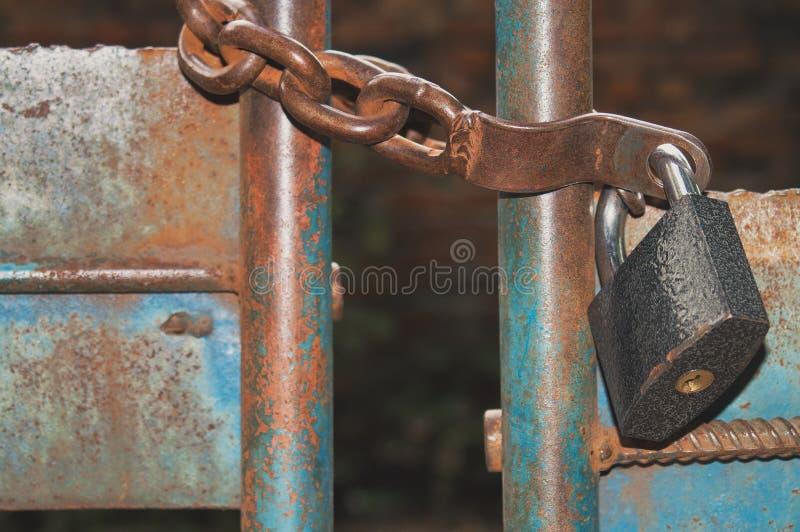 Altes rostiges Vorhängeschloß auf der Kette hängt an geschlossenen Toren lizenzfreie stockfotografie