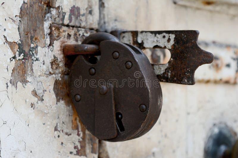 Altes rostiges Vorhängeschloß auf einer verwitterten Tür lizenzfreie stockfotos