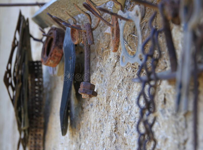 Altes rostiges Werkzeug auf einem alten Aufhängerhaken stockfotografie