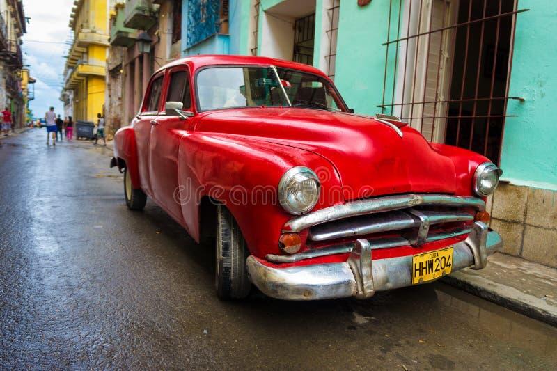 Altes rotes Auto in einer schäbigen Straße in Havana stockbild