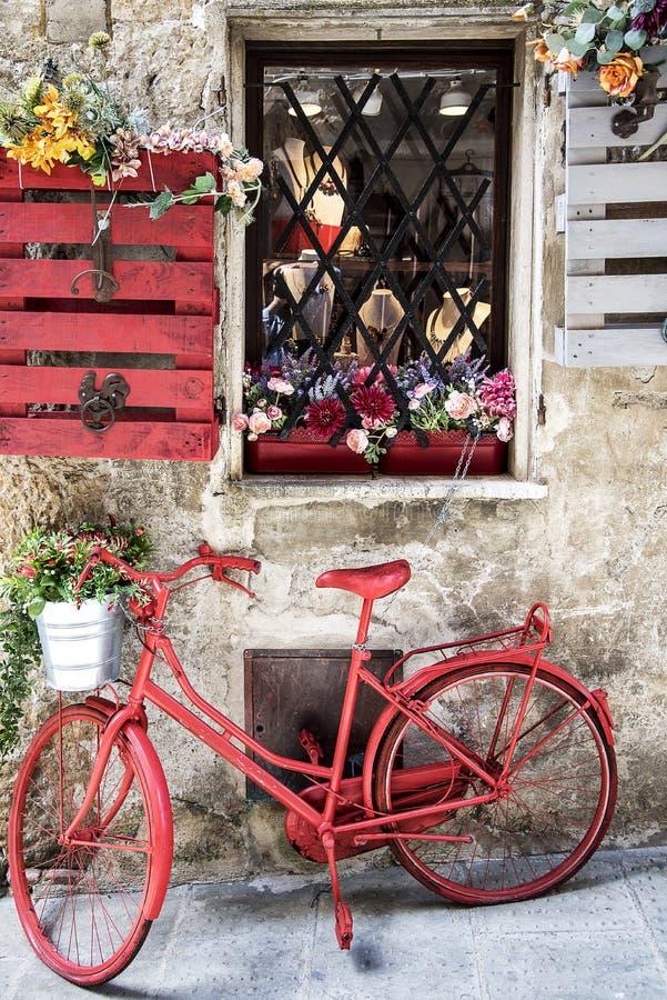 Altes rotes Fahrrad in der Straße stockfotografie