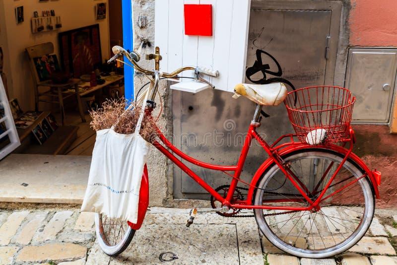 Altes rotes Fahrrad an der System-Tür in Rovinj stockfotos