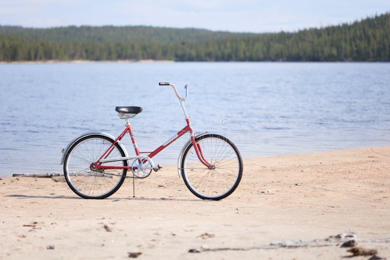 Altes rotes Fahrrad fotografiert auf Strand lizenzfreies stockbild