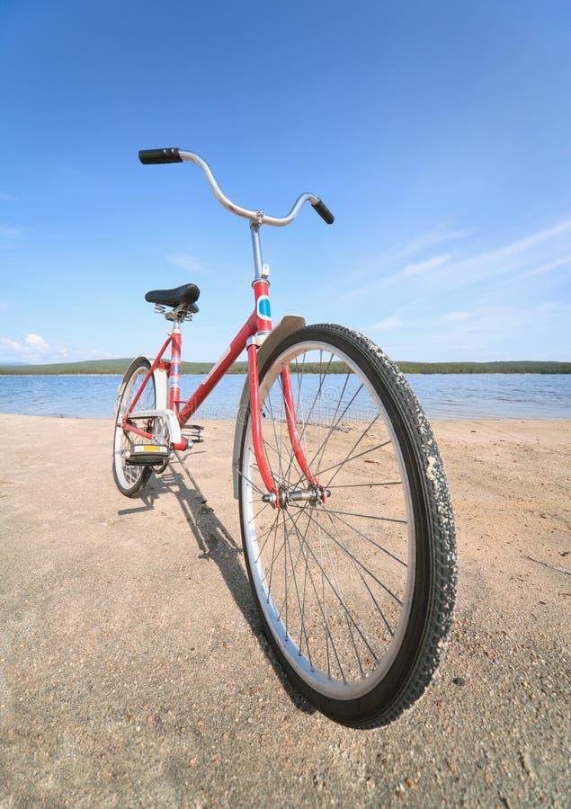 Altes rotes Fahrrad fotografiert auf Strand lizenzfreies stockfoto