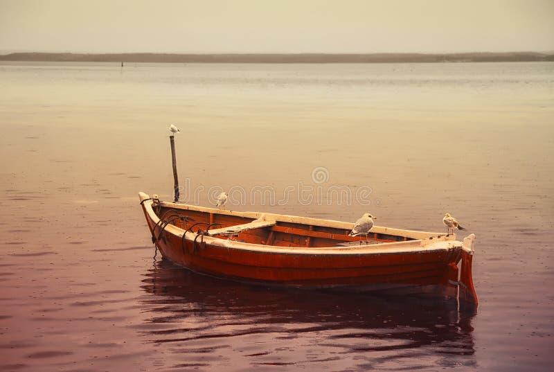 Altes rotes Fischerboot, das am Pier mit den Seemöwenvögeln sitzen auf den Seiten steht lizenzfreies stockbild