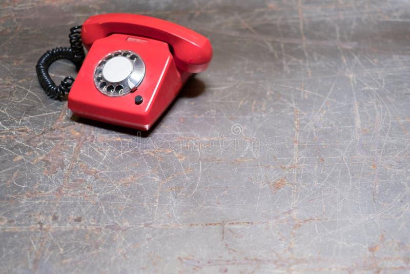 Altes rotes Telefon auf Tabelle - Weinlesetelefon auf Schreibtisch stockfotografie