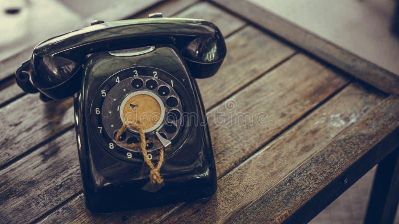 Altes schwarzes Telefon auf Holztisch lizenzfreies stockfoto