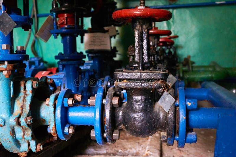 Altes schwarzes Ventil mit roten Griffen auf der blau-gemalten Rohrleitung des kalten Wassers lizenzfreie stockfotografie