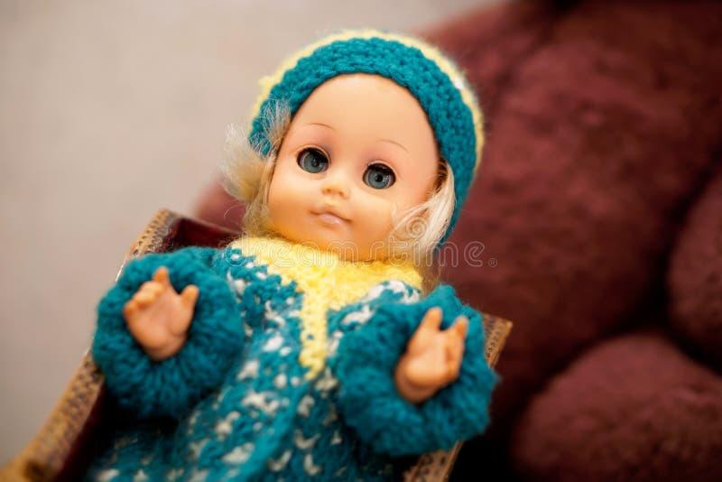 Altes Spielzeug ist eine Weinlesepuppe mit blauen Augen in einem woolen Hut Einzelteil von der Vergangenheit stockfoto