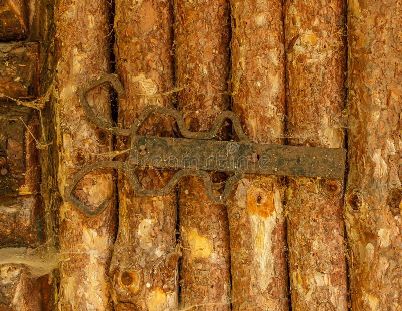 Altes staubiges rustikales verwittertes Eisenabhängung von der Holztür stockbilder