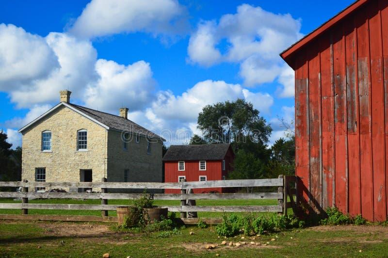 Altes Steingebäude mit zwei roten Scheunen-Gebäuden lizenzfreies stockfoto