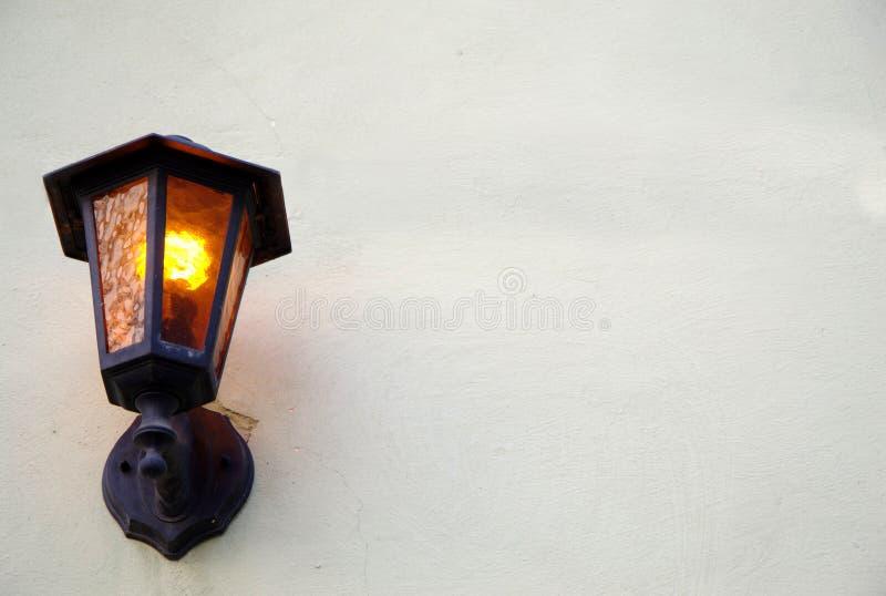 Altes Straßeneisen beleuchtete Lampe auf einfacher Wand lizenzfreies stockbild