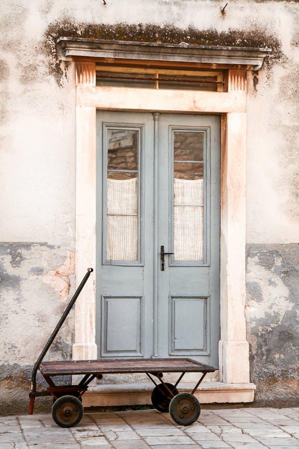 Altes Türhaus mit rostiger Laufkatze vor Eingang lizenzfreie stockfotos