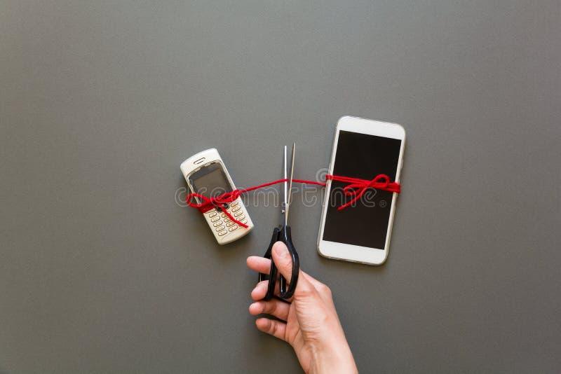 Altes Telefon und neuer Smartphone schlossen durch den roten Impuls an, der auf grauen Papierhintergrund legt Scheren schnitten d stockfotos