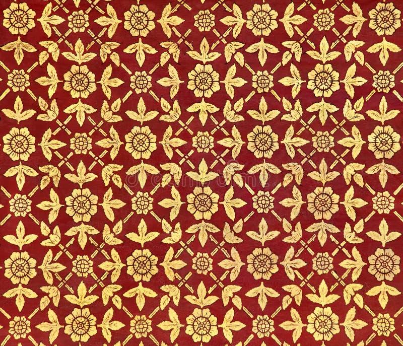 Altes thailändisches Design auf der Decke eines Palastes mit Mustern von goldenen Blättern und von Blumen auf rotem Hintergrund lizenzfreie stockfotos