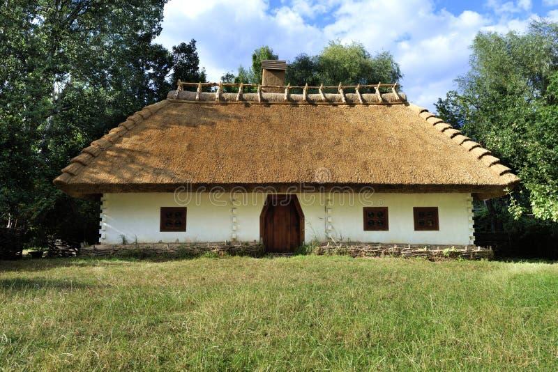 Altes traditionelles ukrainisches l?ndliches Haus mit Strohdach- und Flechtweidenzaun im Garten lizenzfreie stockbilder