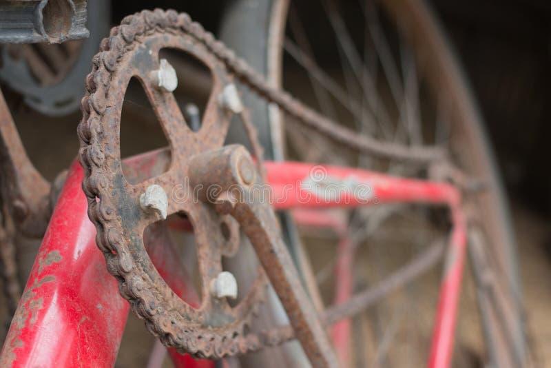 Altes und rostiges rotes Fahrrad umgab undeutlichen Hintergrund stockbild