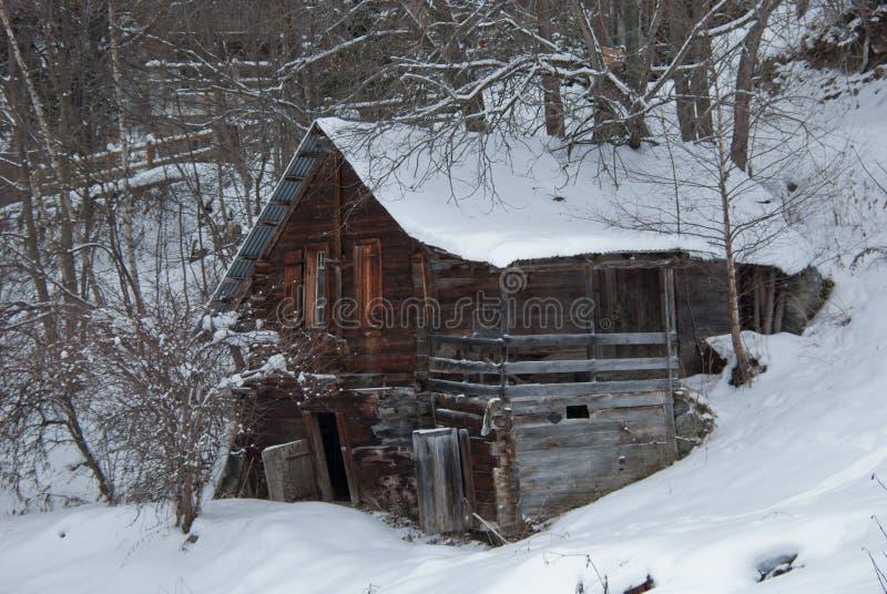 Altes und verlassenes Blockhaus des Winters in den Alpen stockbild