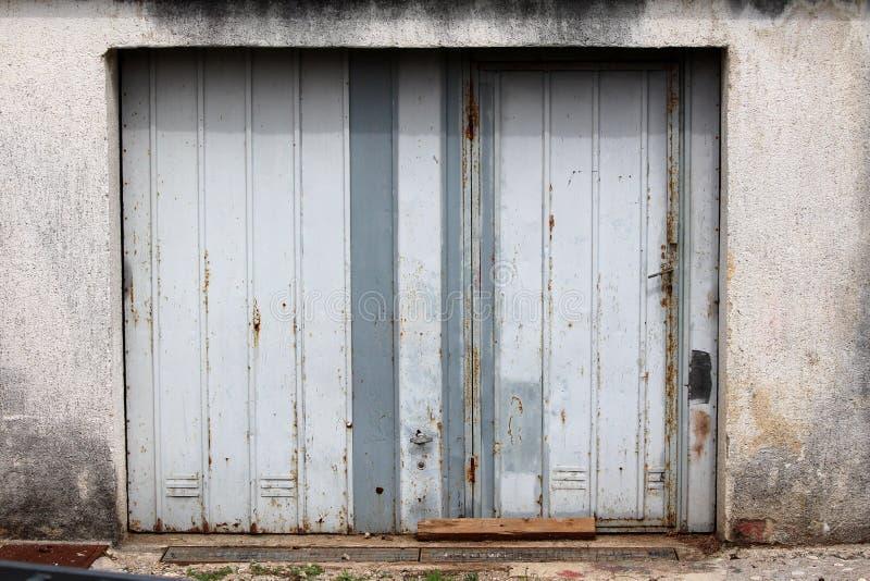 Altes verfallen verrostete teilweise die grauen Metallgaragentoren, die an der Betonmauer nahe bei Betonstraße angebracht wurden lizenzfreies stockbild