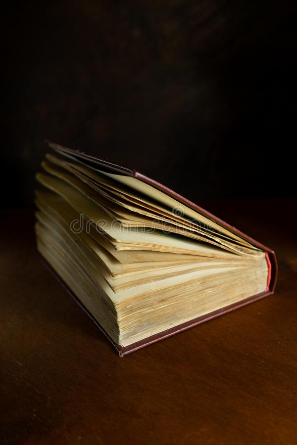 altes verfallenes Buch in einer halben Drehung liegt auf einem dunklen hölzernen Hintergrund lizenzfreies stockbild