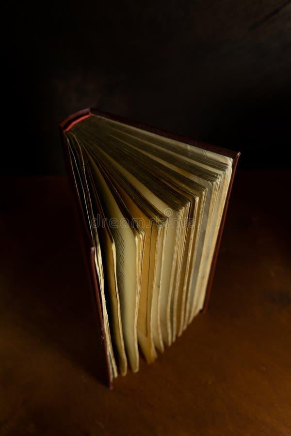 altes verfallenes Buch mit Gelben Seiten in einer vertikalen Position auf einem dunklen Hintergrund stockfotos