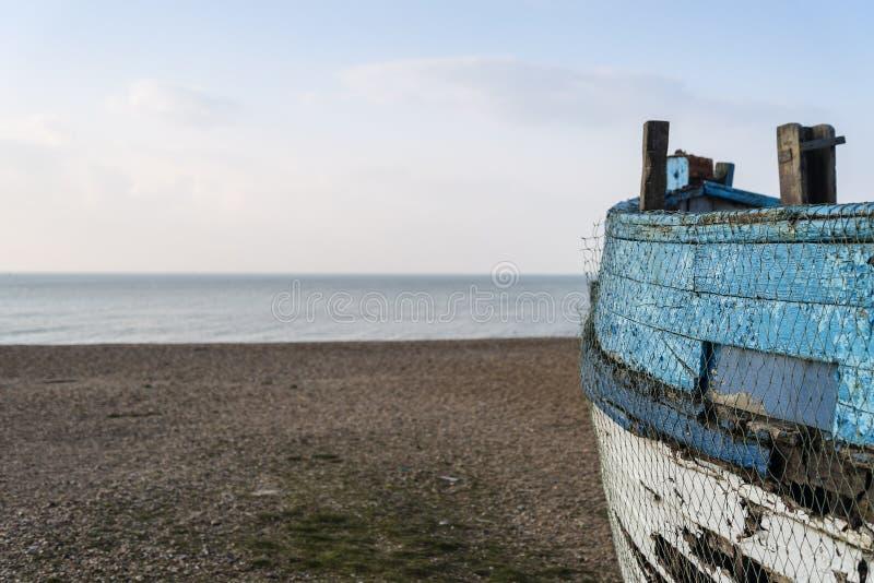 Altes verlassenes Fischerboot auf Strand mit überlegter flacher Abteilung lizenzfreies stockfoto