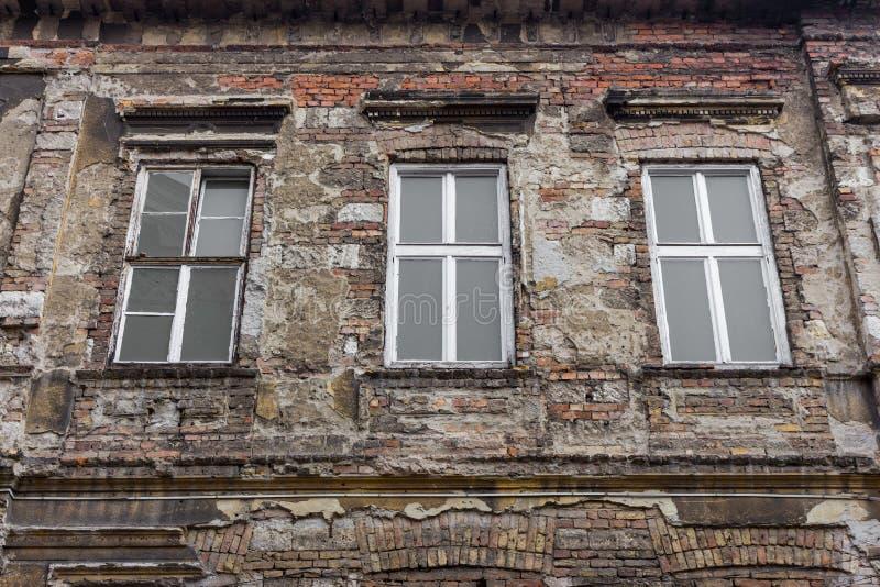 Altes verlassenes Gebäude mit drei Fenstern Gealterte Backsteinmauer Weinlesearchitekturkonzept Altes Haus lizenzfreies stockfoto