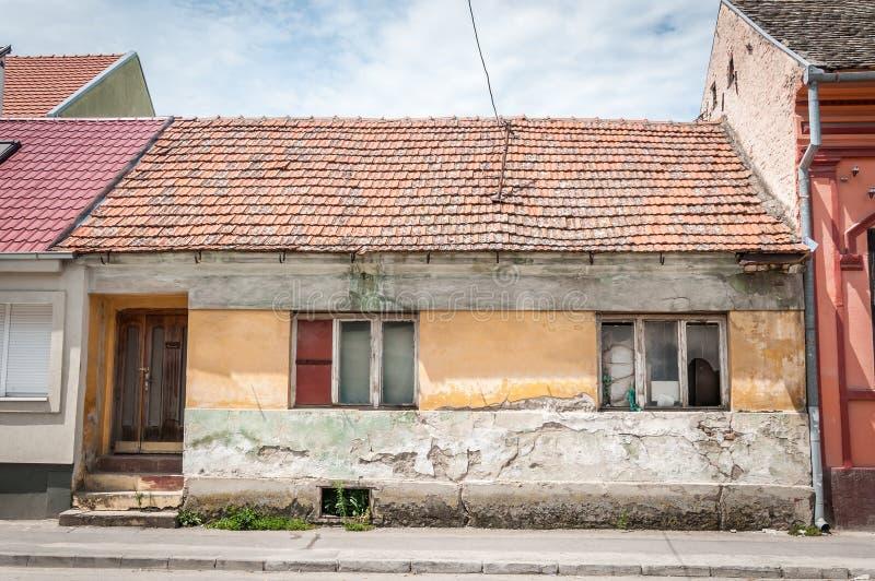 Altes verlassenes Haus mit den defekten und schädigenden Fenstern in der Stadt ruiniert durch Alter stockbild